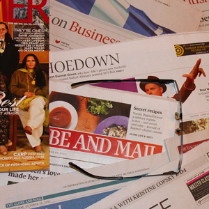 Photograph of newspapers and magazines with a pair of glasses