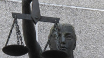 Photograph of woman holding the scales of justice symbol